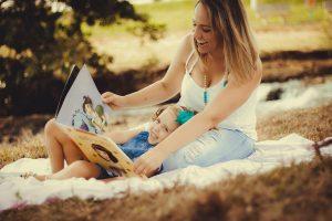 Mère et enfant lisant un livre dans un parc